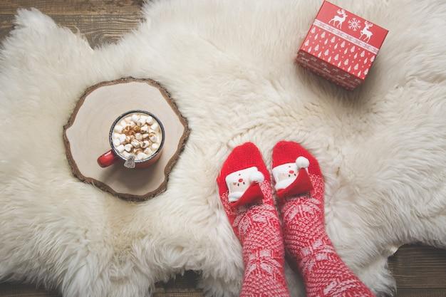 Nogi w ciepłych skarpetach z dzianiny bożonarodzeniowej, filiżanka kawy i prezent.