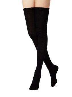 Nogi w czarnych bawełnianych rajstopach na białym tle