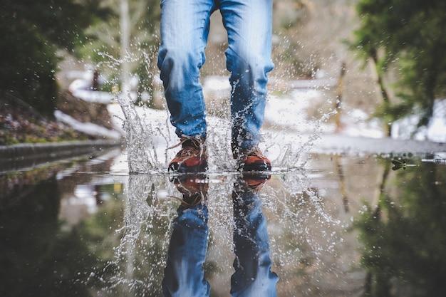 Nogi w niebieskich dżinsach i brązowych butach chodzące po mokrej ulicy
