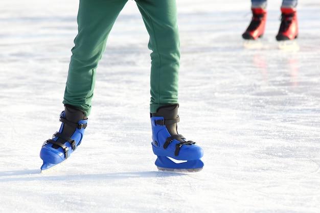 Nogi w niebieskiej jeździe na łyżwach na lodowisku