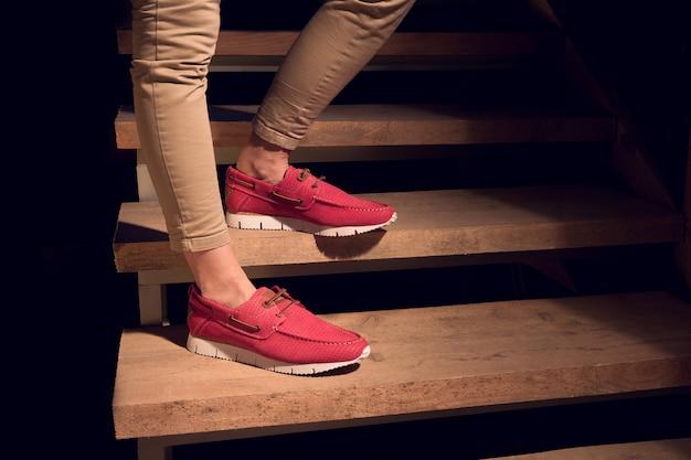 Nogi z czerwonymi skórzanymi mokasynami na schodach