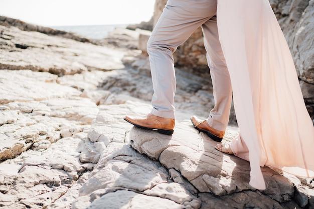 Nogi zakochanych stojących na skałach obok siebie z bliska