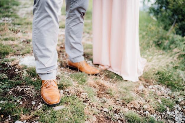 Nogi zakochanych stojących na trawie obok siebie z bliska