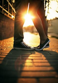 Nogi zbliżenie miłości para o zachodzie słońca