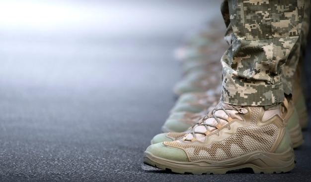 Nogi żołnierzy ubrane są w botki i spodnie moro.