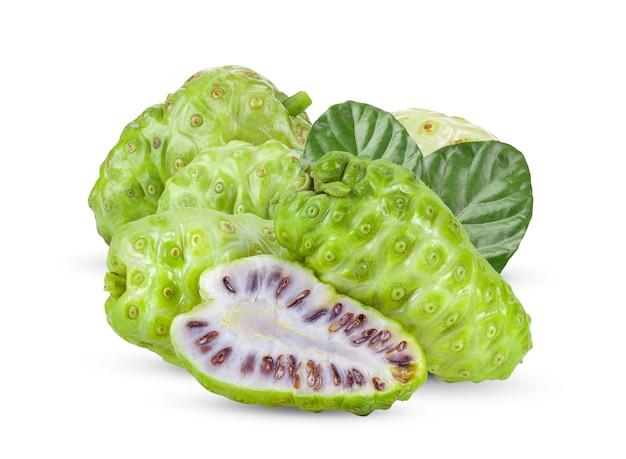 Noni owoc z liśćmi na biel ścianie.