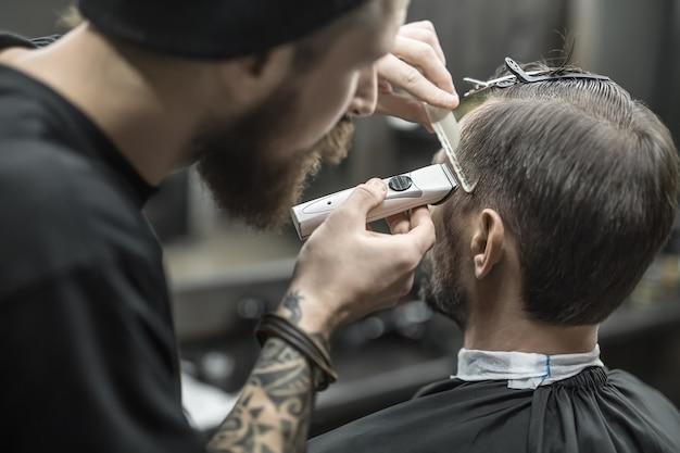 Nonpareil fryzjer z brodą i tatuażem obcina włosy brodatemu klientowi w salonie fryzjerskim