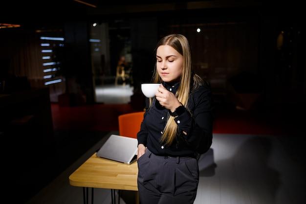 Normalny dzień roboczy nowoczesnej kobiety biznesmena. piękna młoda kobieta trzymająca filiżankę kawy siedząc w swoim miejscu pracy