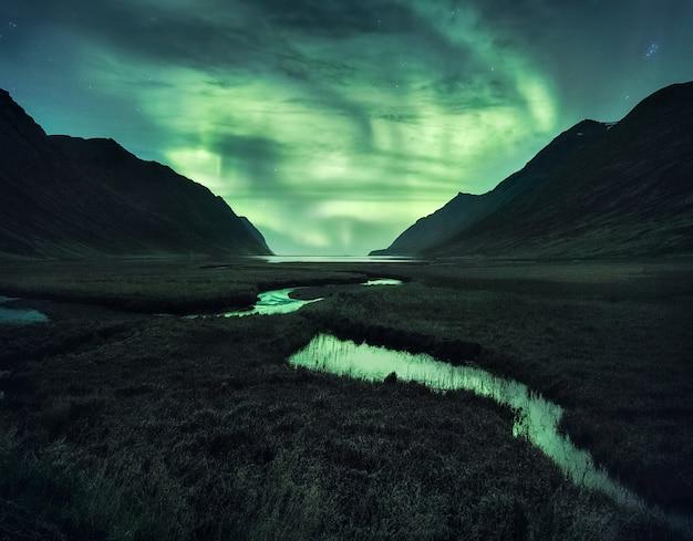 Northen lights pod górami. piękny naturalny krajobraz na islandii.