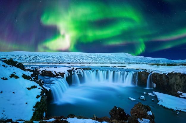 Northern light, aurora borealis przy wodospadzie godafoss w zimie, islandia.
