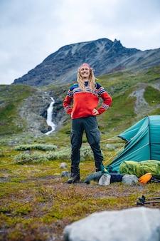 Norweg z dredami stojący przed namiotem w górach