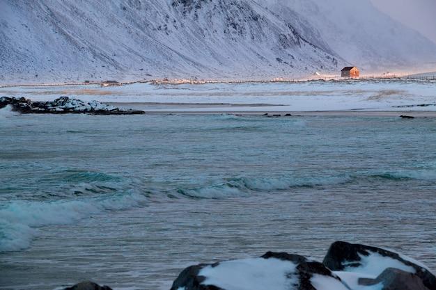 Norwegia. lofoty. zima w pobliżu ramberg. góry i surfować. promień słońca oświetlił samotny dom