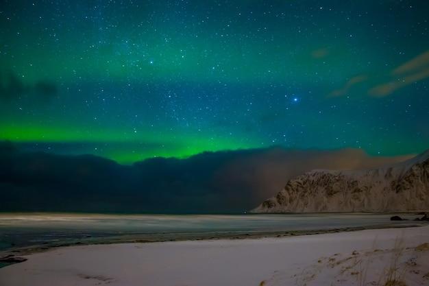 Norweskie lofoty. nocna zimowa plaża fiordu otoczona ośnieżonymi górami. na niebie jest wiele gwiazd, chmur i zorzy polarnej