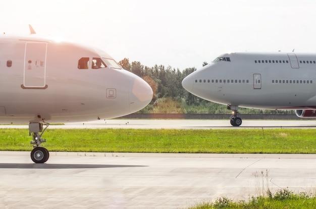 Nos przed nosem dwa samoloty na pasie startowym na lotnisku.