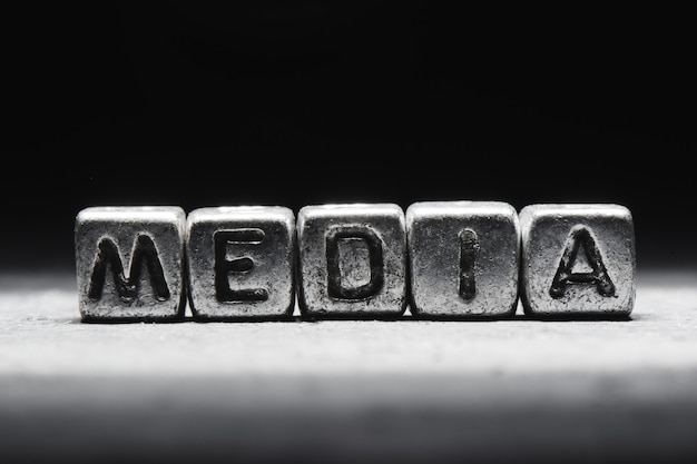 Nośniki koncepcyjne napis na metalowych kostkach na czarnym szarym tle z bliska na białym tle
