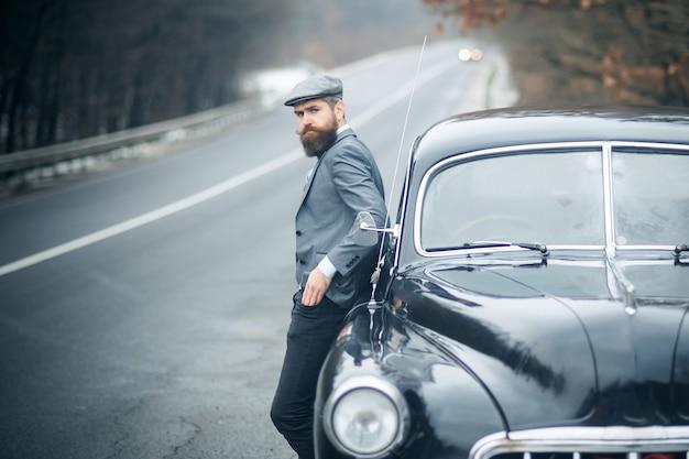 Nostalgia i retro samochód u brodatego mężczyzny. stary facet.
