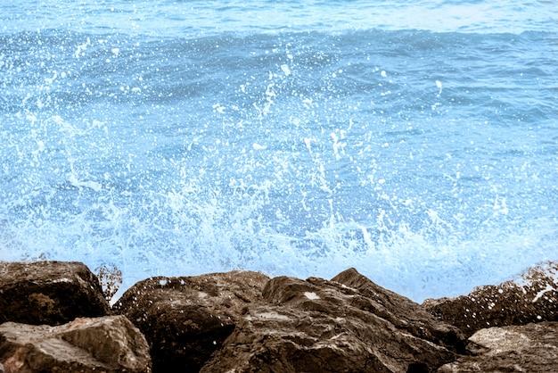 Nostalgiczna morska scena fal rozpryskujących skały