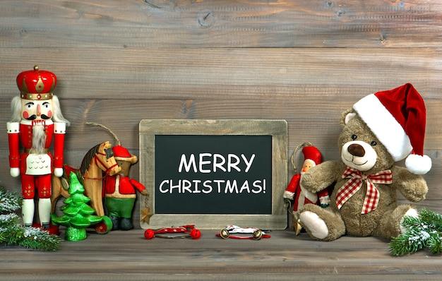 Nostalgiczne świąteczne dekoracje z zabytkowymi zabawkami i tablicą na tekst. stonowany obraz w stylu retro z przykładowym tekstem wesołych świąt