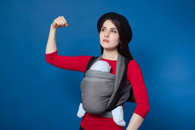 Noszenie atrakcyjna młoda matka z dzieckiem w tkanej nosidełku demonstruje biceps. wolna ręka, aktywna i wewnętrzna koncepcja silnego macierzyństwa