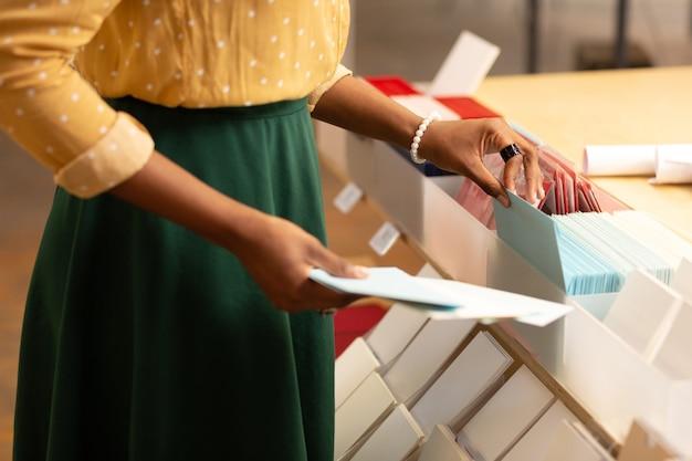 Noszenie białej bransoletki. zbliżenie pracownika magazynu papierniczego noszącego białą bransoletkę wkładającą koperty
