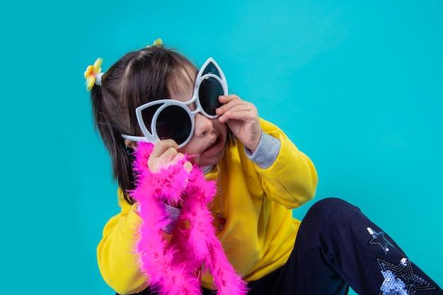 Noszenie kolorowych okularów. niezwykła dziewczyna z zaburzeniami psychicznymi jest modna w okularach przeciwsłonecznych i trzyma boa