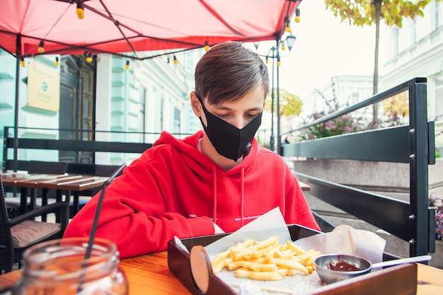 Noszenie masek w miejscach publicznych. młody mężczyzna siedzi w ulicznej kawiarni w masce ochronnej i patrzy na frytki.