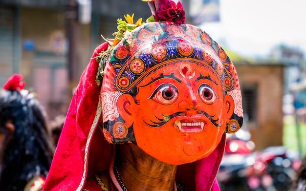 Noszenie maski na twarz podczas tradycyjnego festiwalu tańca nil barahi w nepalu
