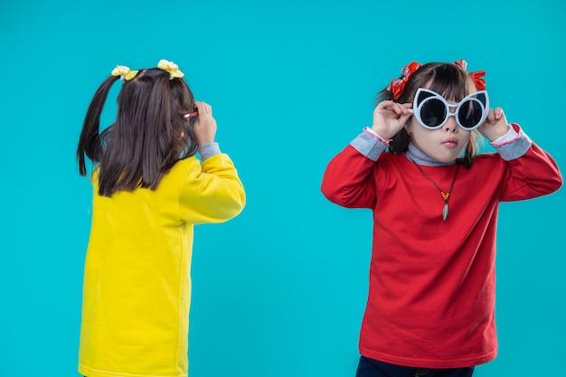 Noszenie okularów dla dorosłych. zainteresowane krótkowłose dziewczyny z zaburzeniami psychicznymi przymierzające gigantyczne okulary przeciwsłoneczne w kolorowych bluzach z kapturem