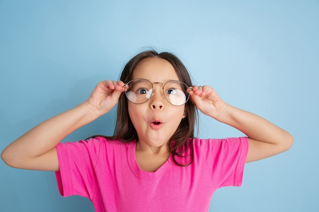 Noszenie okularów. kaukaski portret małej dziewczynki na niebieskiej ścianie. piękna modelka w różowej koszuli.
