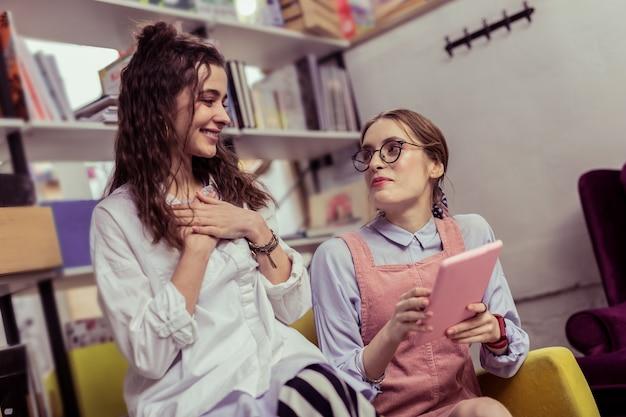 Noszenie różowego laptopa. przyciągające pozytywne panie prowadzące przyjemną, przyjemną rozmowę podczas siedzenia w strefie relaksu