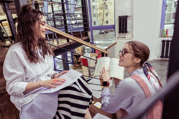 Noszenie stylowych strojów. wyrazista jasnowłosa dziewczyna z podekscytowaniem pokazująca fragment książki uśmiechniętej ciemnowłosej przyjaciółce