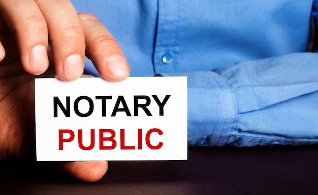 Notariusz publiczny jest zapisany na białej wizytówce w dłoni mężczyzny