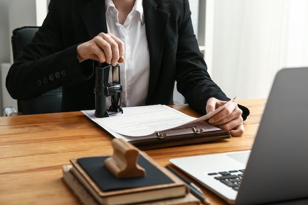 Notariusz stempluje dokument w biurze