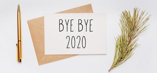 Notatka bye bye 2020 z kopertą, gałązką świerku i złotym długopisem na białej powierzchni