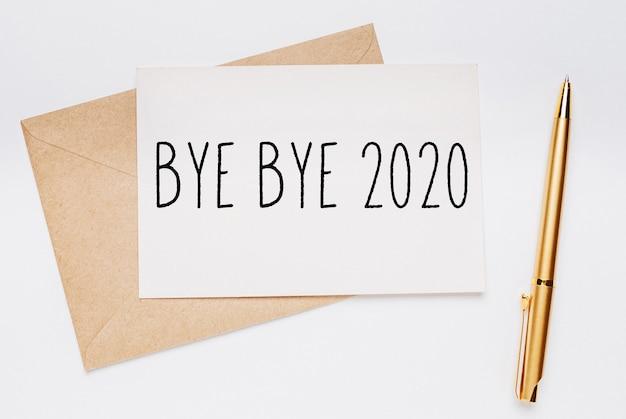 Notatka bye bye 2020 z kopertą i złotym długopisem na białej powierzchni. wesołych świąt i nowego roku koncepcja