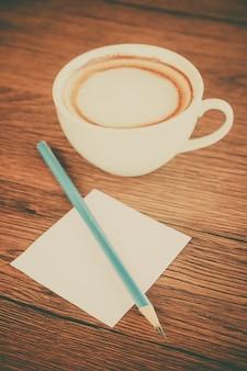 Notatka papierowa z ołówkiem i filiżanką kawy