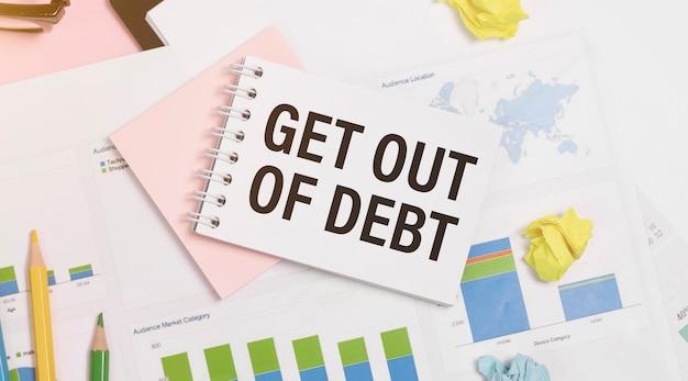 Notatka papierowa z tekstem get out of debt