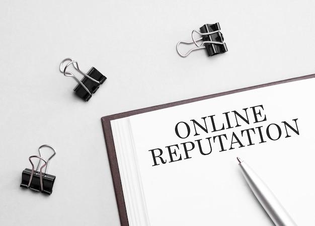 Notatka papierowa z tekstem reputacja online, pióro i narzędzia biurowe, białe tło. pomysł na biznes