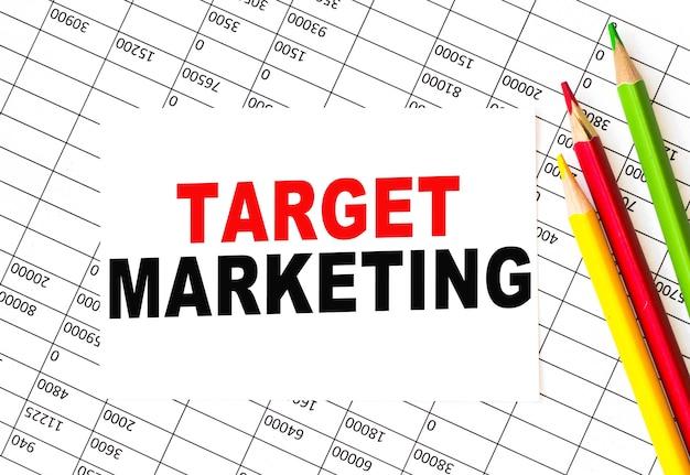"Notatka ""target marketing"" i kolorowe kredki nad raportem"