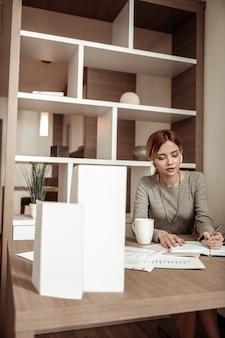 Notatki w terminarzu. piękna pracowita bizneswoman robi notatki w swoim terminarzu po dniu roboczym