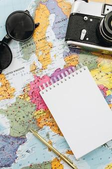 Notatki z podróży makieta. mapa europy, aparat, okulary przeciwsłoneczne i notatnik. widok z góry na płasko