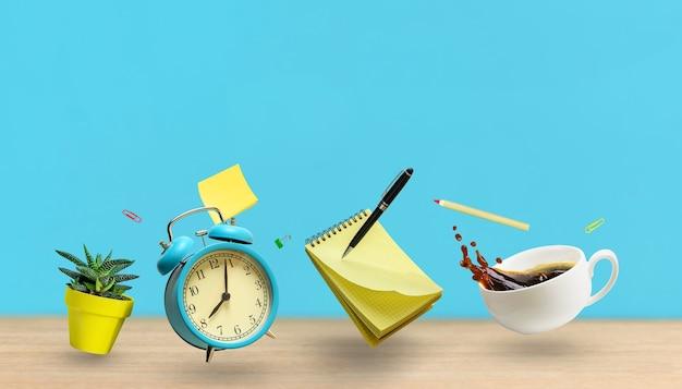 Notatnik akcesoria biurowe, budzik, filiżanka kawy, roślina, pióro latające nad stołem biurkowym na tle niebieskiej ściany. makieta z miejscem na kopię