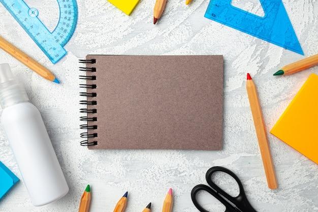 Notatnik, artykuły papiernicze i odkażacz do rąk widok z góry na biurku