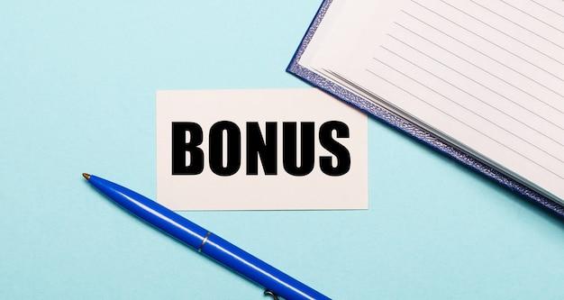 Notatnik, biały długopis i karteczka z napisem bonus na niebieskiej powierzchni