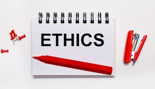 Notatnik, biały długopis i kartka z napisem ethics na niebieskim tle. widok z góry