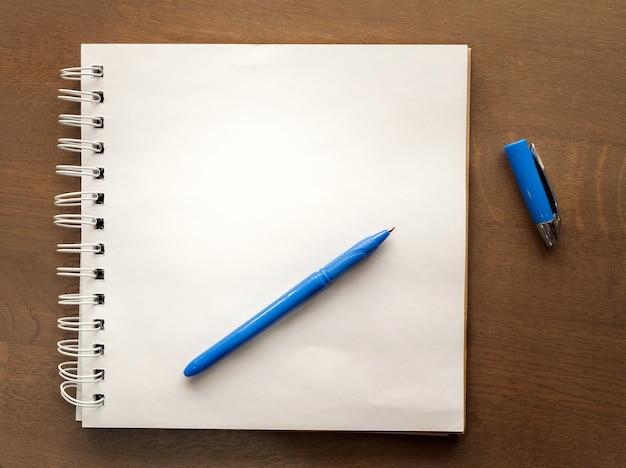 Notatnik biurkowy niebieski stojak na długopisy na drewnianym stole