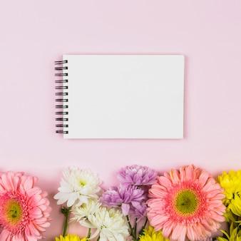 Notatnik blisko jaskrawych aromatycznych świeżych kwiatów