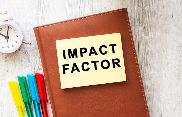 Notatnik brązowy, naklejka z napisem impact factor, kolorowe długopisy, zegar na drewnianym tle. pomysł na biznes.
