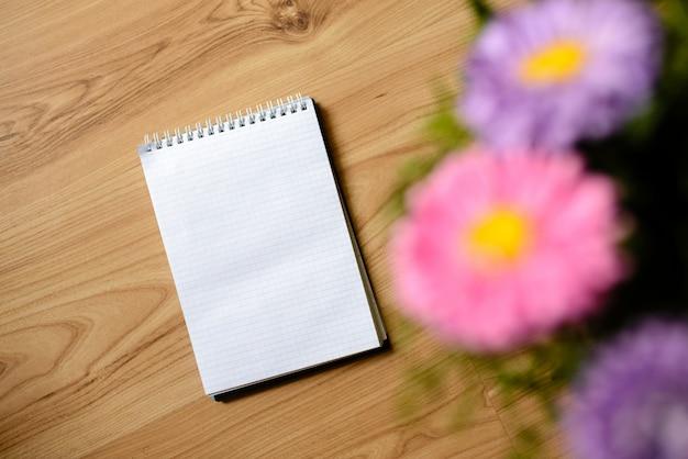 Notatnik dla wpisów z kwiatami na stole.