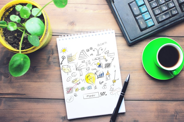 Notatnik, długopis, filiżanka kawy i kalkulator na drewnianym stole